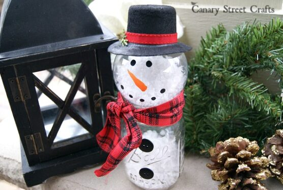A snowman made from a mason jar and a clear plastic ornament