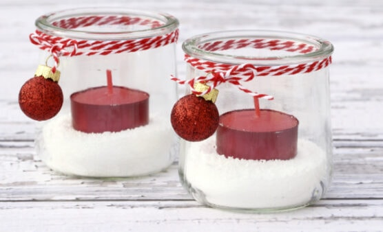 Two decorated mason jars with candles inside them