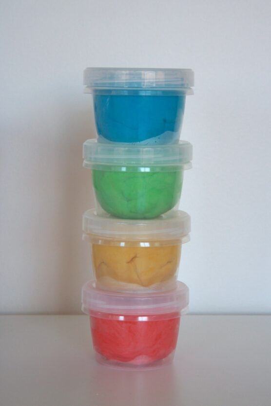 Blue, green, yellow, and red playdough in small containers