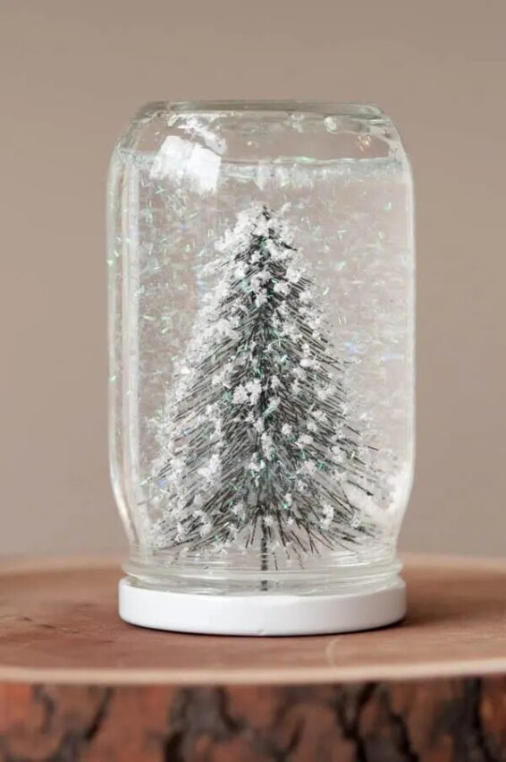 Tree and white glitter inside a clear jar